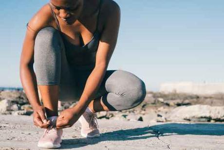 close up photo of woman in gray tank top and gray leggings tying her shoes