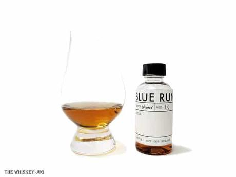 White background tasting shot with a Blue Run Bourbon Whiskey (winter) sample bottle and a glass of whiskey next to it.