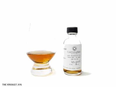 White background tasting shot with the Castle and Key Restoration Rye sample bottle and a glass of whiskey next to it.