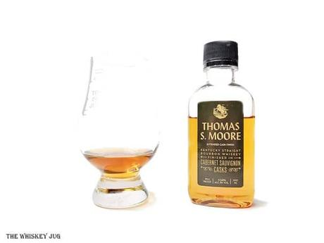 White background tasting shot with a sample bottle of the Thomas S. Moore Bourbon Cabernet Sauvignon Casks and a glass of whiskey next to it.