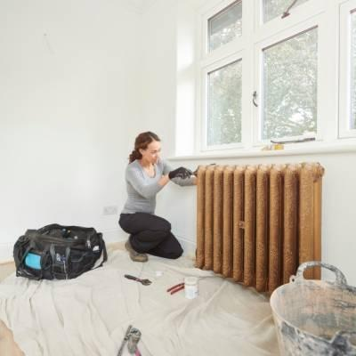 woman installing a cast iron radiator
