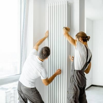 two men installing a vertical central heating radiator