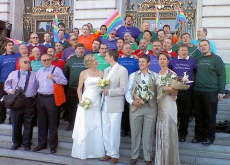 The San Francisco Gay Men's Chorus performs on the steps of San Francisco City Hall as gay couples marry inside.