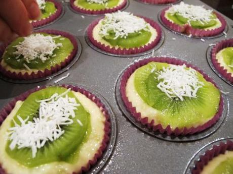 Uncooked muffins in trays, being topped with kiwifruit and coconut