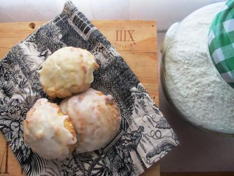 Three buttermilk cookies, one a cloth with a flour jar next to it