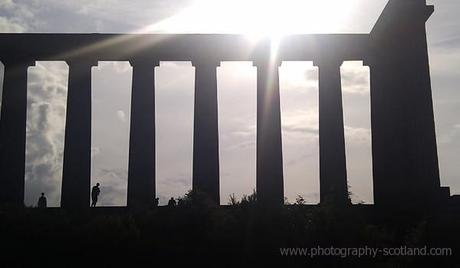 Photo - people standing on Calton Hill folly, silhouetted against a bright sky