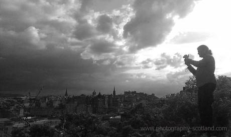 Photo - photographer taking a picture of the Edinburgh skyline from Calton Hill in the city centre