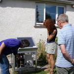 David Henshaw pointing out details of a small-scale solar hot water system