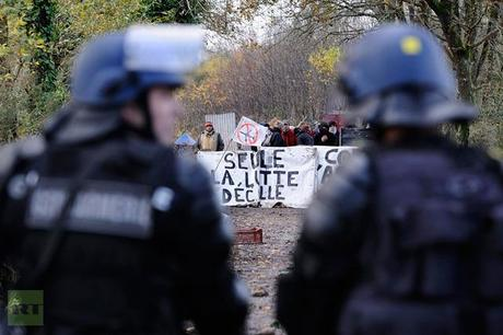 French anti-riot police officers stand in front of protesters holding a banner partially reading ′′Only the fight takes off′�