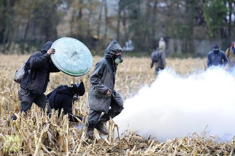 Protesters run on November 24, 2012 from tear gas shot by French riot police, seeking to evict squatters from protected swampland where Prime Minister Jean-Marc Ayrault wants to build a new airport (AFP Photo / Jean-Sebastuen Evrard)