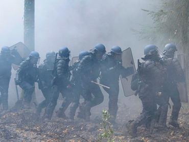 French anti-riot police officers walk through smoke from tear gas, on November 24, 2012 in Notre-Dame-des-Landes as they seek to evict squatters from protected swampland where Prime Minister Jean-Marc Ayrault wants to build a new airport (AFP Photo / Jean-Sebastuen Evrard)