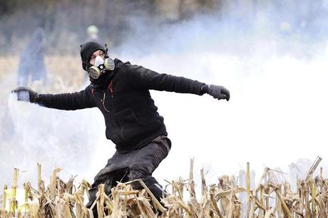 A protester faces on November 24, 2012 French riot police, seeking to evict squatters from protected swampland where Prime Minister Jean-Marc Ayrault wants to build a new airport (AFP Photo / Jean-Sebastuen Evrard)