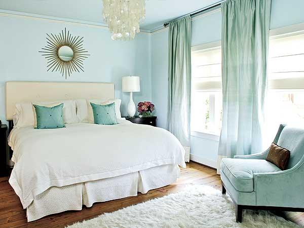 Sky blue bedroom with white bedding, starburst mirror and silk draperies