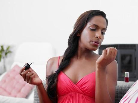 woman applying red nail varnish on sofa