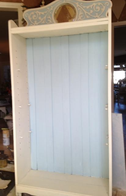 an antique bookcase revamped with off white and pale blue paint