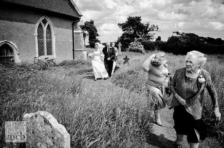 A windy arrival for the bride at her Suffolk country church