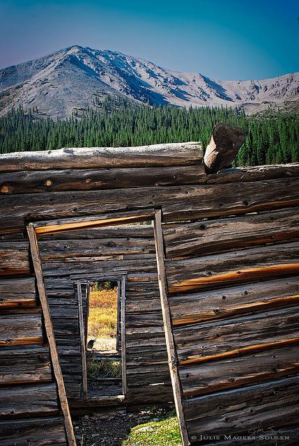 a rustic abandoned cabin with three crooked doorways