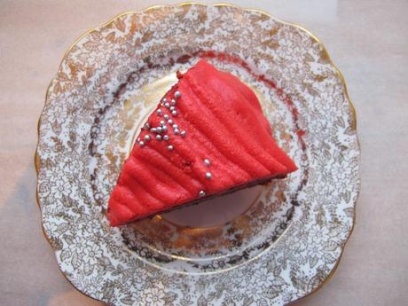 A slice of red velvet cake with red icing on a plate