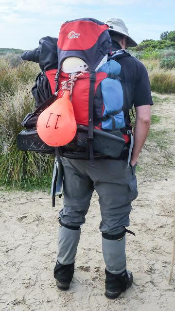 backpack with helmet, buoy and flipper strapped on exterior