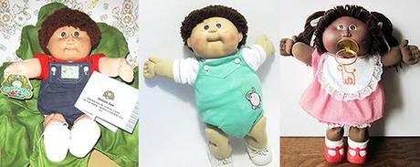 three Cabbage Patch Dolls from the early 1980s, one with cabbage leaf and certificate information card, a baby, and a black African American little girl wearing bib and sucking pacifier