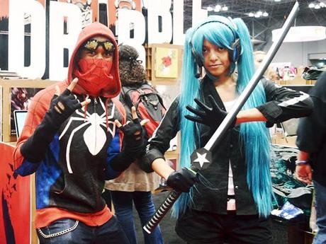 couple wearing Spiderman and ninja manga superhero costumes and posing in front of RedBubble booth at 2012 New York Comic Con comics and pop culture convention