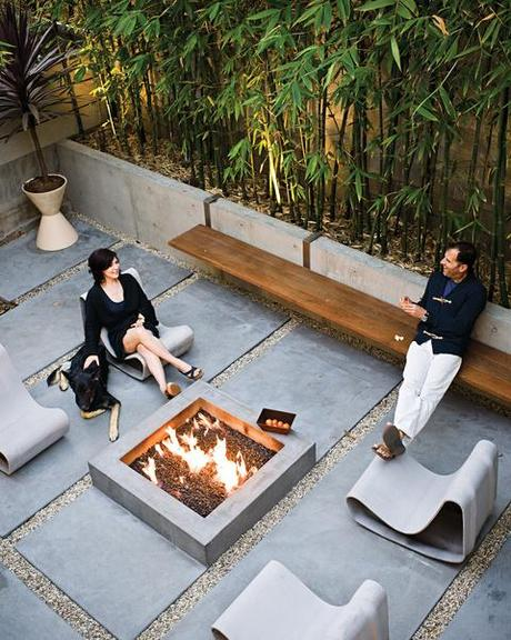 Backyard fireplace area with a long steelandipe bench and Willy Guhl