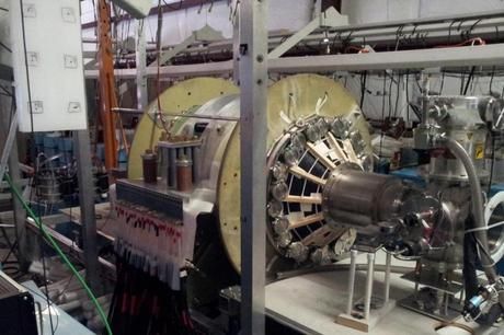 The fusion driven rocket test chamber at the UW Plasma Dynamics Lab in Redmond. The green vacuum chamber is surrounded by two large, high-strength aluminum magnets. These magnets are powered by energy-storage capacitors through the many cables connected to them. (Credit: University of Washington, MSNW)