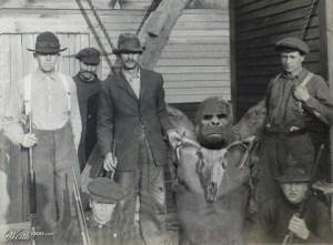 An extremely bizarre photo, apparently only recently recently surfaced, showing a purported dead Bigfoot being hold up with cables and surrounded by the men who killed it.