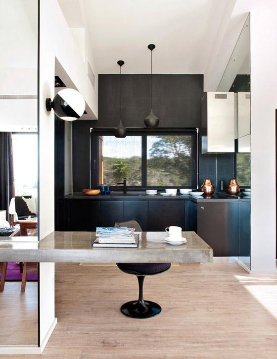 Portugal mod summer home, Nuno Benito, kitchen, contemporary black cabinets, concrete counter, Tom Dixon pendants, Saarinen chair