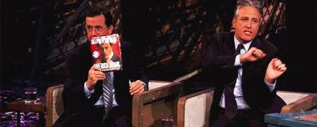 GIF of Jon Stewart and Stephen Colbert. Jon is dancing around adorably in his seat.