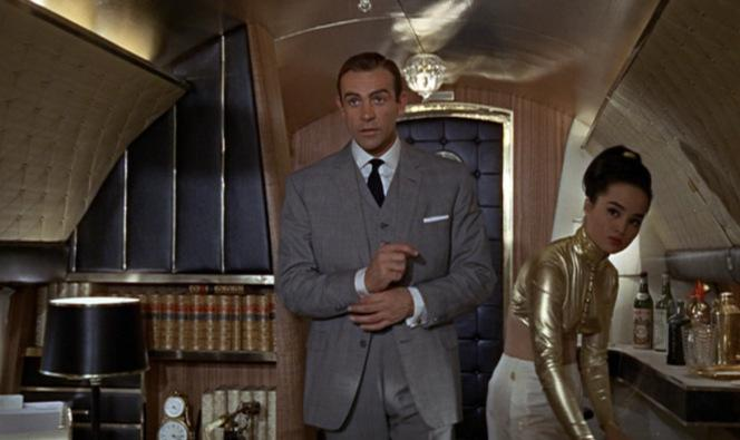 Yeah, I'm sure this is the last place Bond wants to be. A gold-plated plane, a skimpy-dressed Asian stewardess, a well-stocked bar at his disposal, and a busty lesbian pilot. Give me a break.