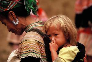 A Hmong woman with, incredibly enough, a blond baby. When I worked with the Hmong, they told me that blond and blue eyed babies were sometimes born to Hmong women, a legacy of their origin in the Tarim Basin long ago.