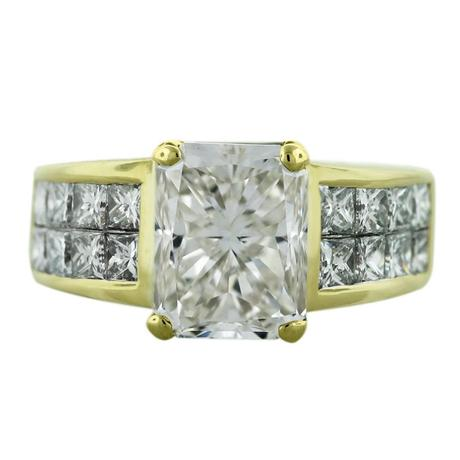 Radiant cut diamond engagement ring set in 18kt yellow gold with invisibly set princess cuts