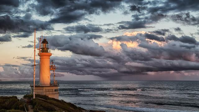 point lonsdale lighthouse with setting sun and rain clouds at sea