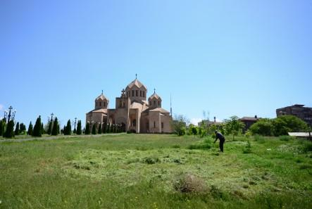 man cutting grass in front of Saint Gregory the Illuminator Cathedral Yerevan