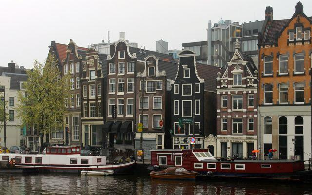 Amsterdam canal with houseboats and historic buildings