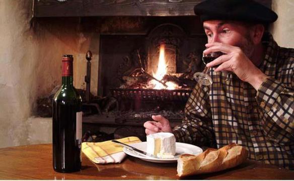 man with a beret drinking wine at a table with bottle of wine glass of wine cheese and baguette in front of open fire, Frankreich, France, Franzose, french