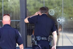 Image: Officers look through a bullet-damaged window of an IHOP restaurant