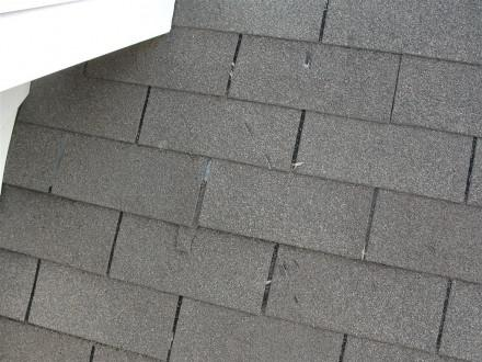 Damaged shingles from ice dam hacks