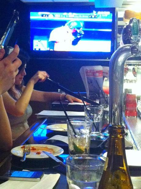 A woman who takes her work - paper cutting tomorrow's handouts - to the bar of a TGIF in Taipei.
