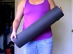 Person holding a black yoga mat.