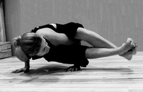 Woman in astavakrasana, a bound hand balancing pose.
