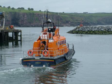 lifeboat leaves harbor from dunmore east in county waterford - ireland