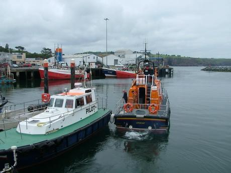 lifeboat and pilot boat leave dunmore east harbor in county waterford - ireland
