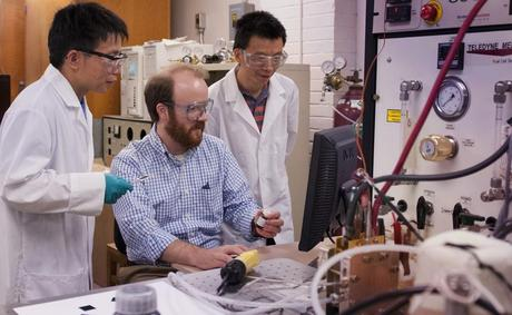 Michael Hickner, seated, along with research associates Yongjun Leng, left, and Nanwen Li review the data received from a specific polymer membrane that has been inserted into the fuel cell test stand. (Credit: Patrick Mansell / Pennsylvania State University)