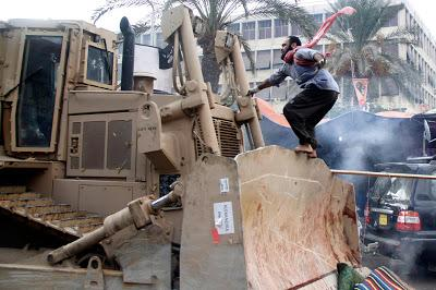 Egyptian Woman Stands In Front Of Bulldozer To Protect Wounded Man As Egypt Explodes In Violence (Stunning Videos & Photos)