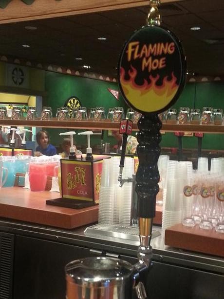 Sitting at the bar. The Flaming Moe is actually nonalcoholic. You can also get Duff, Duff Light, and Buzz Cola.