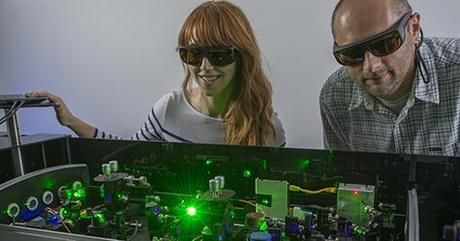 Graduate student Michelle Harris and research scientist Darek Niedzwiedzki in PARC's Ultrafast Laser Facility. The laser setup allows them to measure energy transfer steps among pigments in light-harvesting antennas that take place in a trillionth of a second. (Credit: Joe Angeles / WUSTL)