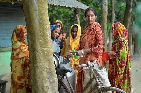 Collecting milk from women dairy farmers in Bangladesh. (Photo: Akram Ali/CARE Bangladesh)