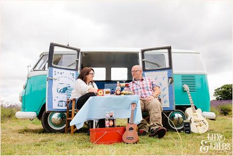 Rocker couple have a picnic in front of their turquoise VW camper van in Mayfield Lavender field